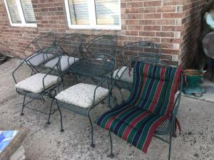 A group of seven metal patio chairs.