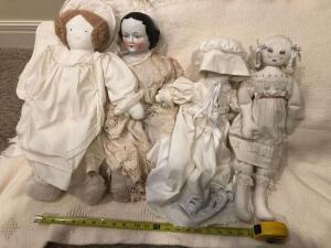 Porcelain black haired doll. Three cloth dolls