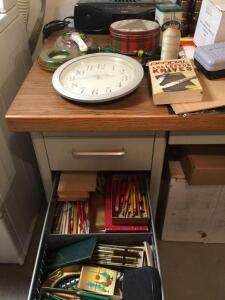 Pencils in left-hand drawers, radio, flashlights, contents on top of desk