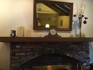 Mirror,  battery chime clock and decorations on mantle