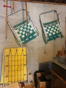 Green and white lawn chairs and camping  bed