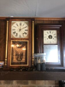 A pair of clocks on the fireplace mantle. 30 inch and 28 inch.